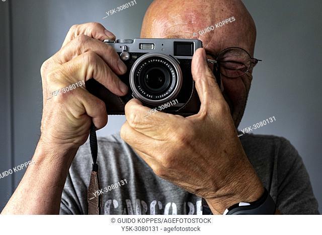 Tilburg, Netherlands. Portrait of a mature adult photogrpaher using a digital, professional compact camera, brand Fuji. Small