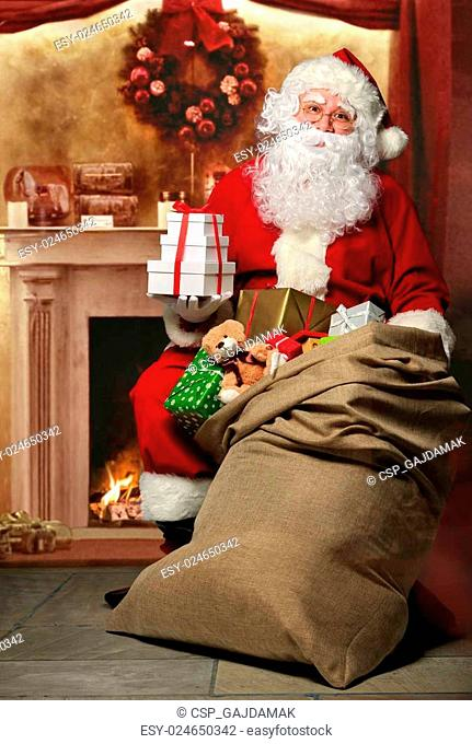 Santa Claus with a bag of presents at the fireplace
