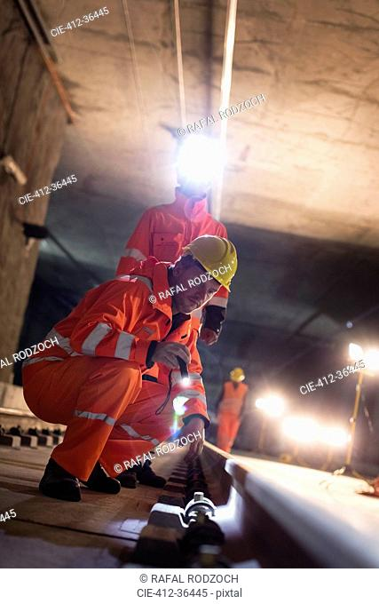 Male construction workers examining underground tracks at dark construction site