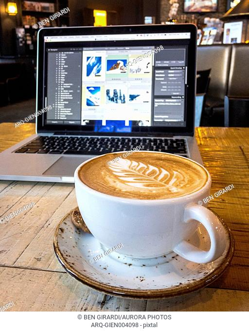 Coffee with froth art and laptop on table