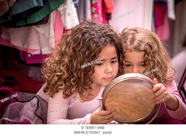 Close up of girls admiring themselves in mirror
