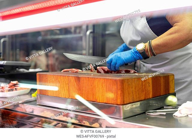Woman slicing ham on chopping block