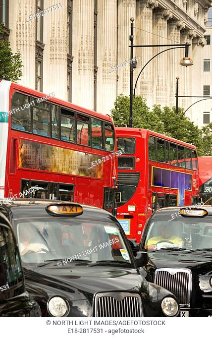 UK, England, London. Iconic London taxicabs and double decker buses in the heart of London