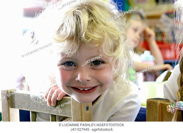4 year old girl at nursery, smiling into camera