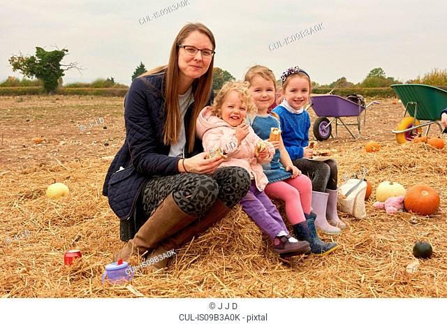 Portrait of mid adult woman and three girls picnicking in pumpkin field