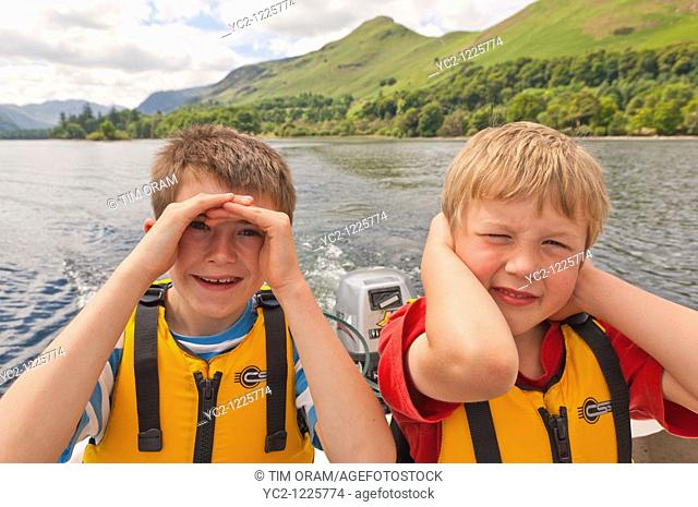 Two young boys in hire boat    at Derwent water at Keswick , Lake District National Park , Cumbria , England , Great Britain , Uk