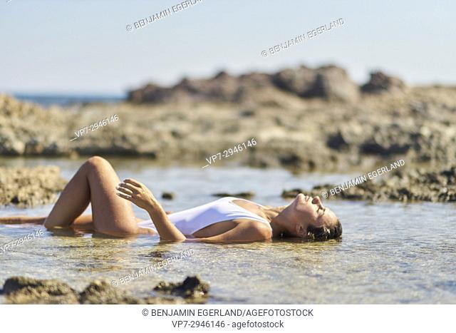 attractive woman enjoying bath in healthy sea water. Dutch ethnicity. At holiday destination Chrissi Island, Crete, Greece