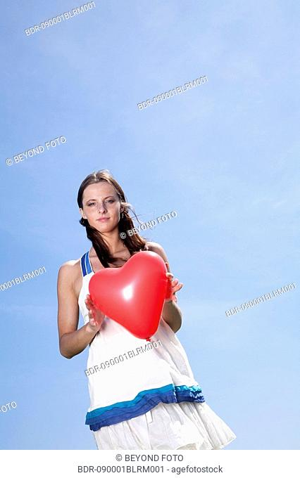 portrait of young woman holding red balloon in shape of heart