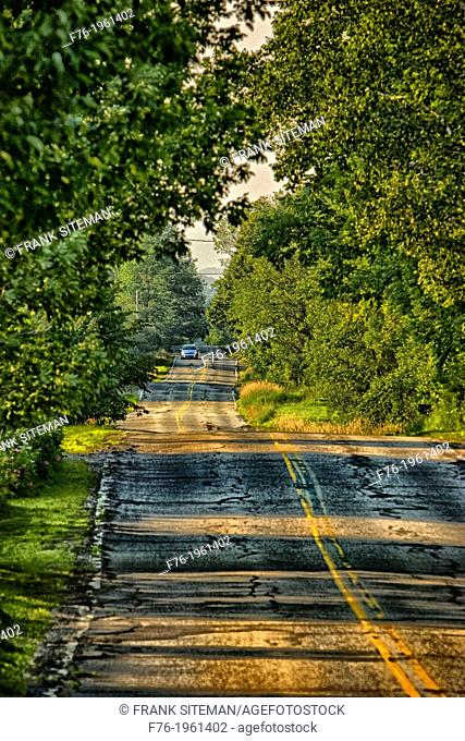 Rural road in Lancaster, NH with car with headlights on approaching, USA