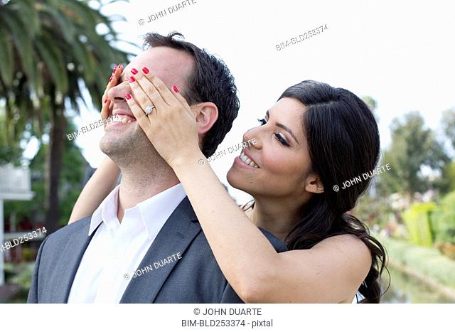 Woman standing behind man covering his eyes