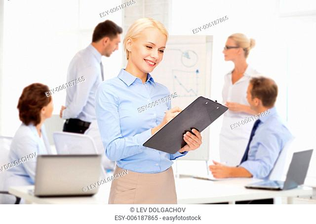 business and education concept - friendly young smiling businesswoman with clipboard and pen