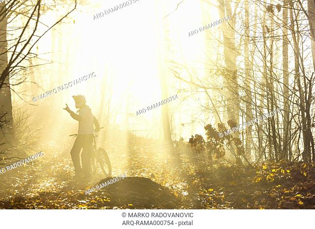 Mountain Biker In Forest During Fog Near City Of Trstenik