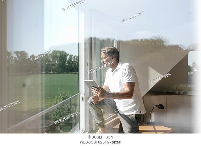 Mature man using tablet at the window