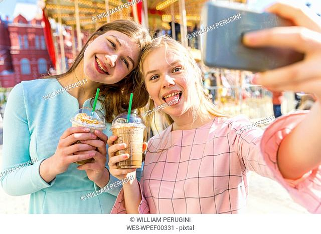Russia, Moscow, teenage girls taking a selfie at funfair