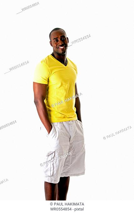 Handsome sporty African American man in yellow shirt and white shorts standing with hands in pocket and big smile, isolated