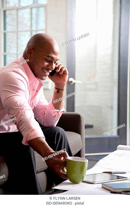 Mid adult man sitting on sofa using mobile phone, smiling