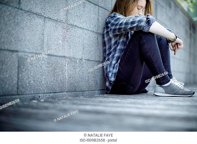 Young woman sitting against wall hugging knees and looking down
