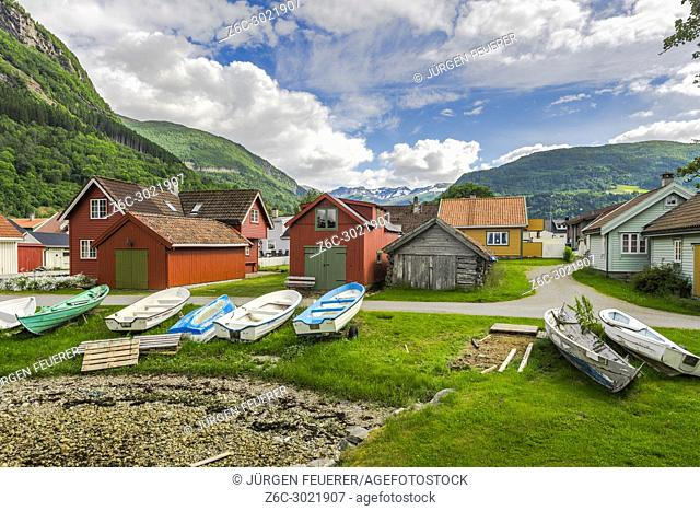colourful huts and boats at the seashore in Vik i Sogn, Norway, snow-capped mountains in background, Sogn og Fjordane