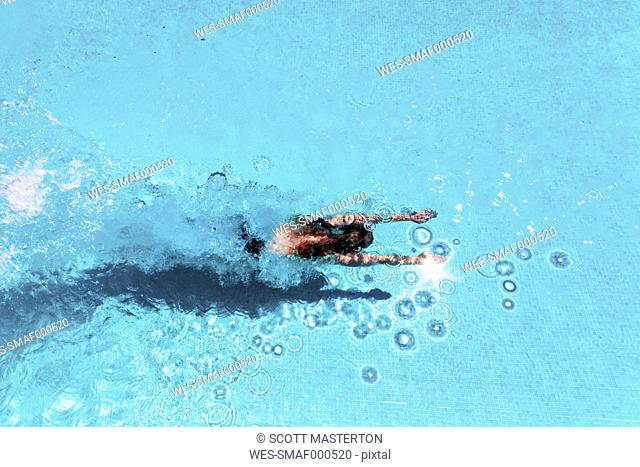 Woman diving underwater in swimming pool