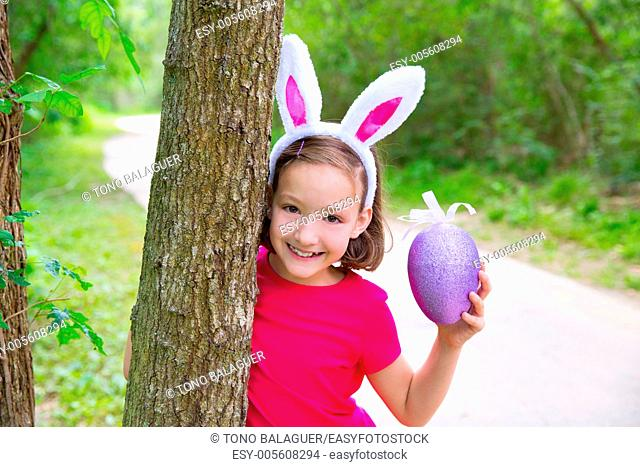 Easter girl with big purple egg and funny bunny ears on the forest