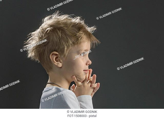Close-up of thoughtful boy with hand on chin against gray background