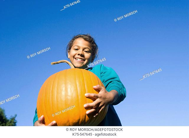 Young girl with big pumpkin