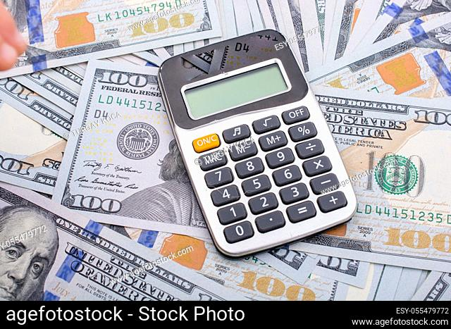 Calculator is placed on the banknote of US dollars spread around