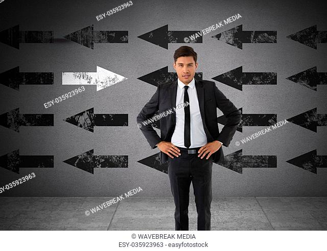 Businessman with arms on hips and arrows in opposite direction