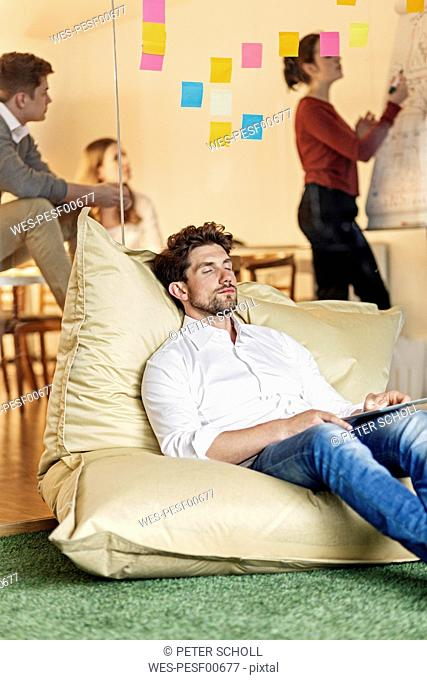 Relaxed man in office sitting in bean bag with meeting in background