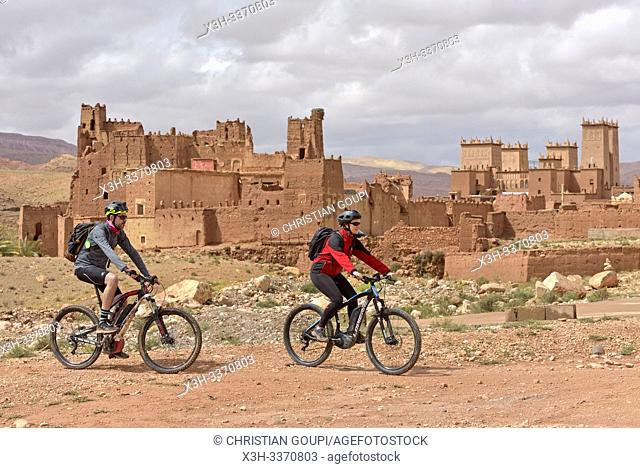 riders on mountain bike with electric assistance in front of the Ksar of Tamedakhte, Ounila River valley, Ouarzazate Province, region of Draa-Tafilalet, Morocco
