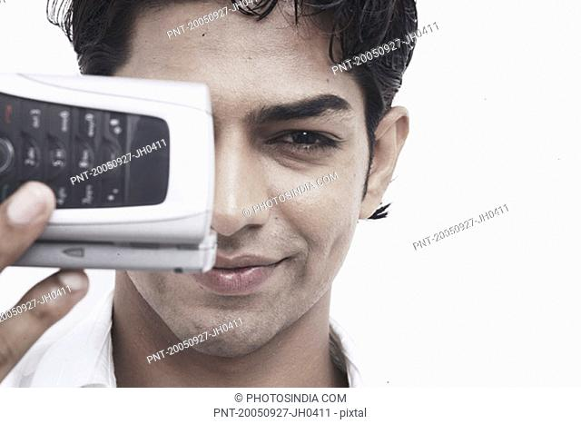 Portrait of a young man holding a mobile phone in front of his face