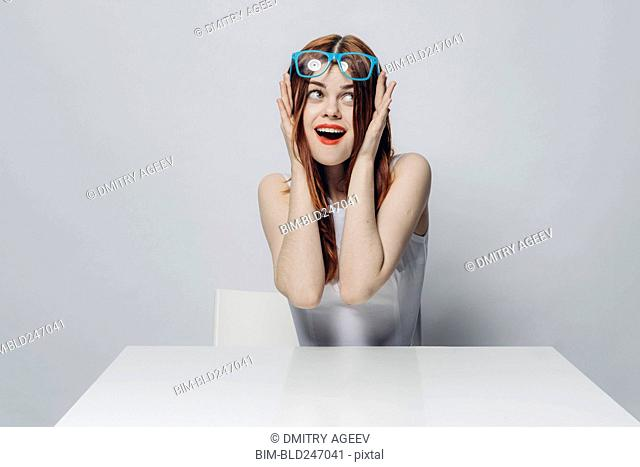 Happy Caucasian woman sitting at table lifting blue eyeglasses