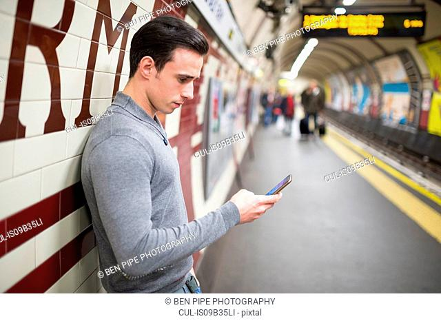 Side view of man on railway platform looking at smartphone