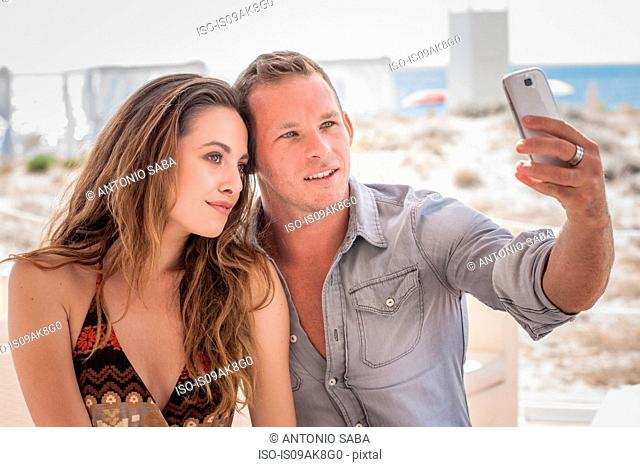 Young couple taking selfie on smartphone at beach, Castiadas, Sardinia, Italy