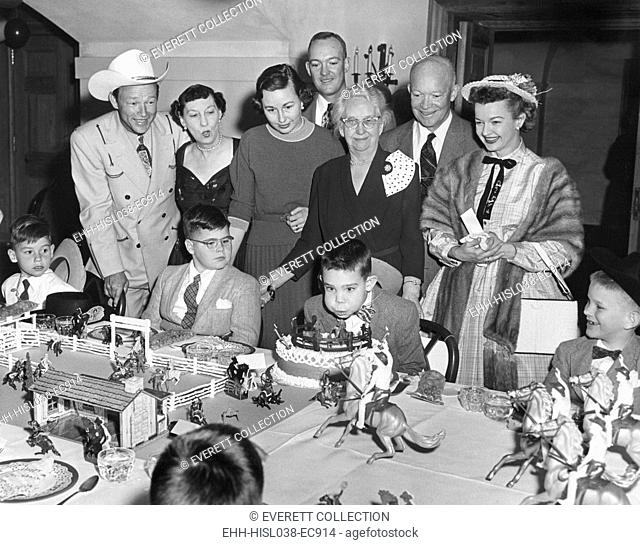 David Eisenhower blows out the candles on his birthday cake. March 31, 1956. Attending his White House birthday party are actors Roy Rogers and Dale Evans and...