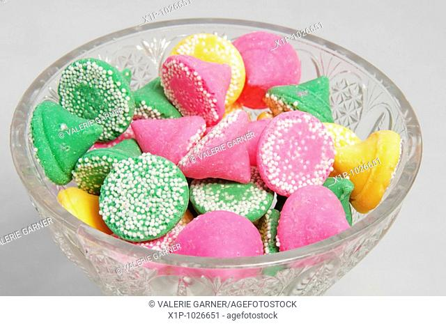 This photo is a crystal dish of pastel colored mints in green, pink and yellow with white polka dots on a white background