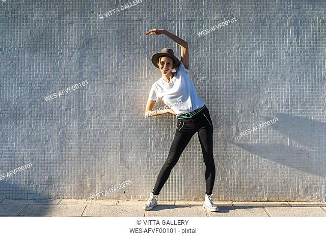 Smiling woman wearing hat standing in front of tiled wall doing stretching exercises