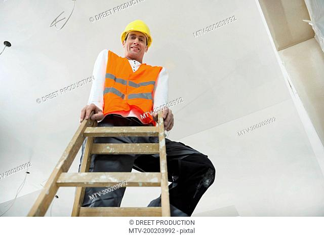 Portrait of construction worker with safety helmet standing on a ladder at construction site of new building