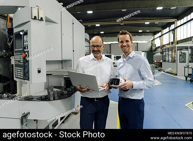 Portrait of two smiling men in a factory with laptop and VR glasses