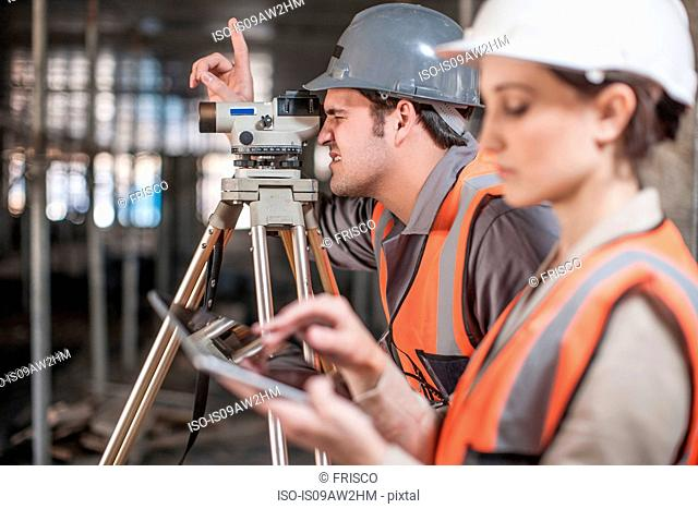 Female and male surveyor using digital tablet and theodolite on construction site