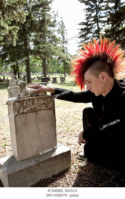 A Young Man Visits A Tombstone In A Cemetery; Edmonton, Alberta, Canada