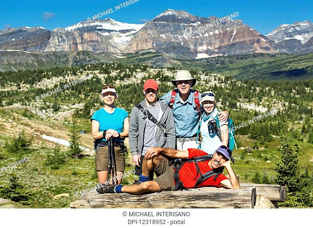 Group of hikers posing on a log bench with valley below and mountains and blue sky in the distance; Banff, Alberta, Canada