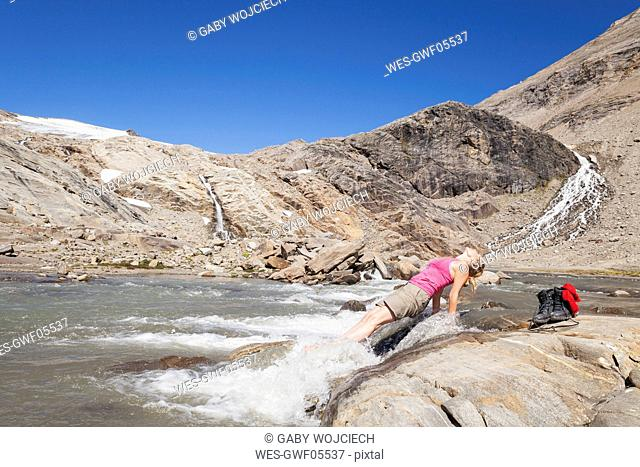 Austria, Carinthia, Grossglockner, Pasterze, woman enjoying refreshing break from hiking, High Tauern National Park