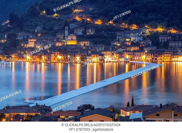 The Floating Piers and Peschiera Maraglio at dusk in Iseo Lake - Italy, Europe