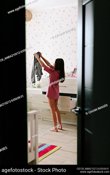 Girl in room picking cloth