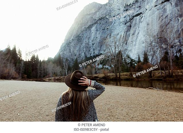 Rear view of woman holding hat looking out at mountain, Yosemite National Park, California, USA
