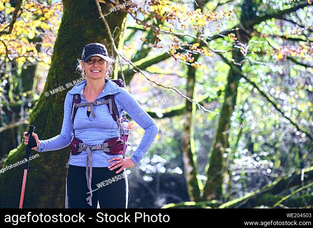 Hiker woman with a walking stick in a beechwood. Urbasa-Andia Natural Park. Navarre, Spain, Europe