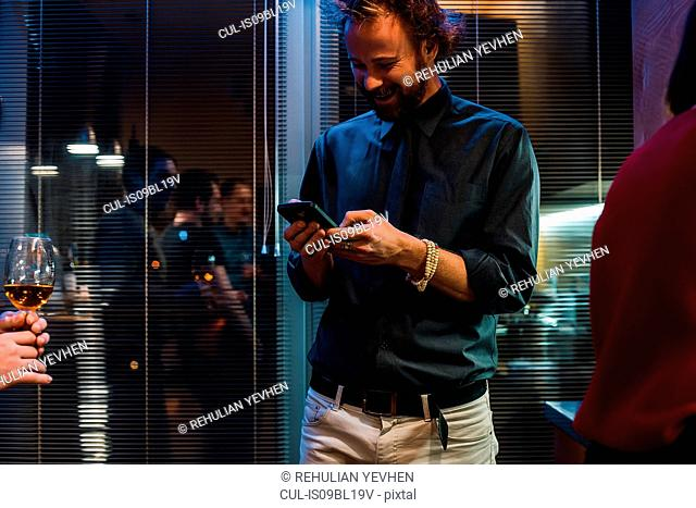 Man using mobile phone at party in apartment