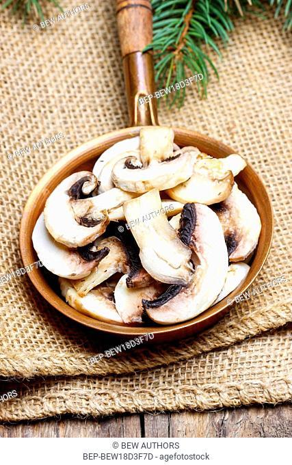Sliced agaricus mushroom on frying pan. Healthy food