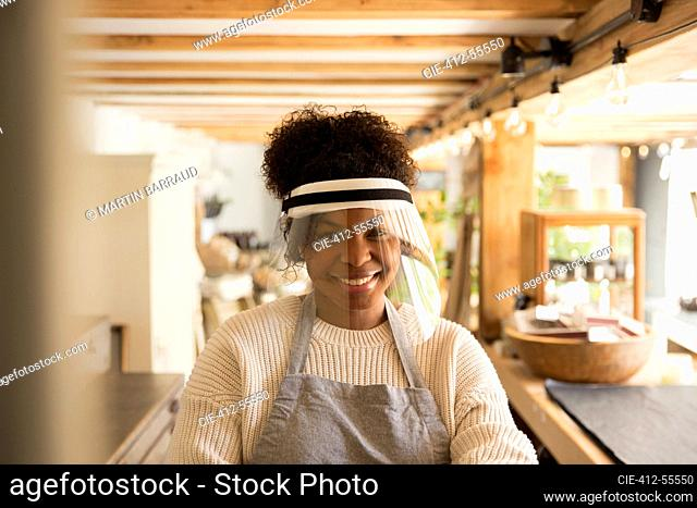 Portrait happy female shop owner wearing face shield